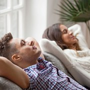 Young couple resting on comfortable couch together at home, happy man and woman enjoying relaxation or nap dozing on sofa with eyes closed, calm family breathing fresh air feeling totally relaxed